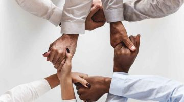 A group of hands holding each other in a circle.