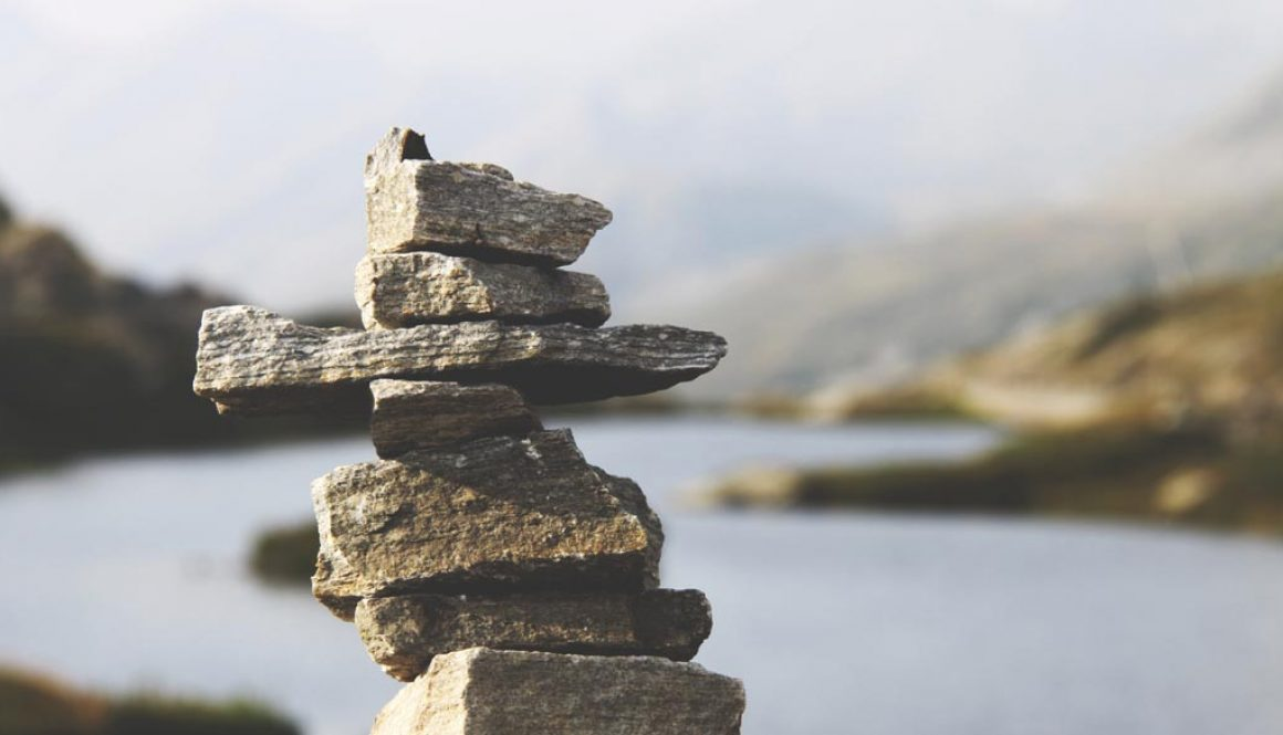 Rocks stacked on top of one another with a river in the background